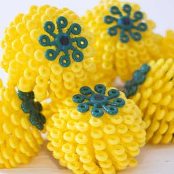 Eight yellow Cora Balls, grouped together in a pile
